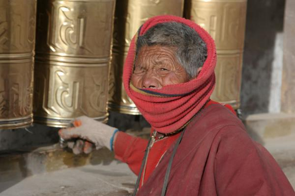 Old woman turning the prayer wheels at Gyanak Mani | Gyanak Mani | China