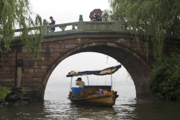 Foto van Boatman going under one of the half-moon bridges on the Su CausewayWest Lake - China