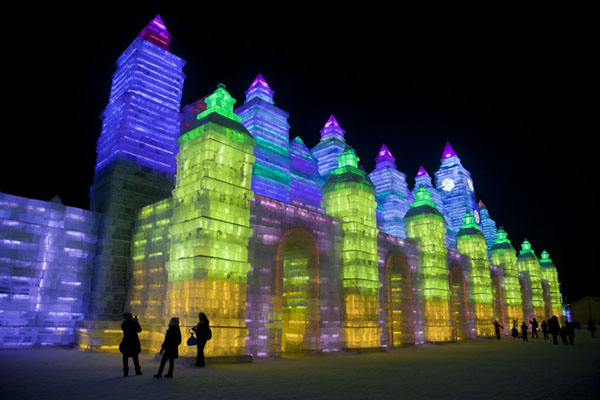 Enormous building made entirely of ice with colourful lights in the evening | Ice and Snow World | China