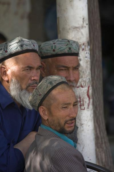 Uyghur men watching the crowd at Hotan bazaar | Hotan Bazaar | China