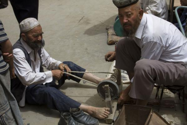 Uyghur men sharpening a knife using their own power | Hotan Bazaar | China