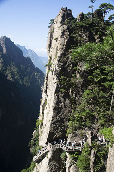 Picture of People walking a trail under a steep cliff in the Yellow Moutains