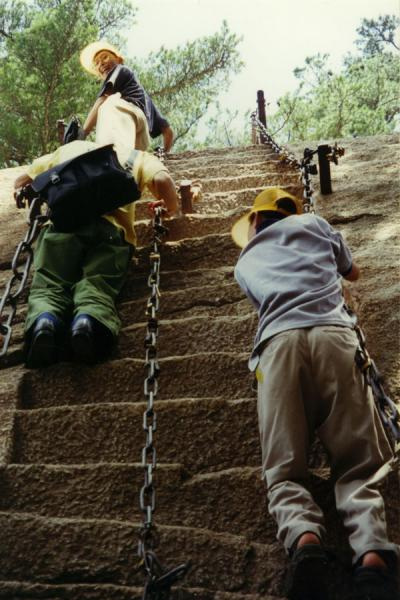People using chains to climb the stairs hewn out in the rocky surface of the Huashan Mountains | Huashan Mountain | China