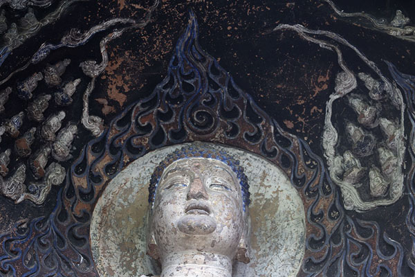 Foto di Close-up of the head of a Buddha in a niche that still has paintJiajiang - Cina