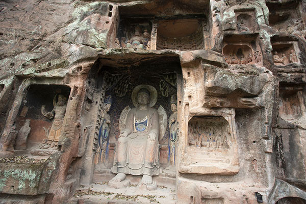 Foto van Looking up the rocky cliff with niches with Buddha statues insideJiajiang - China