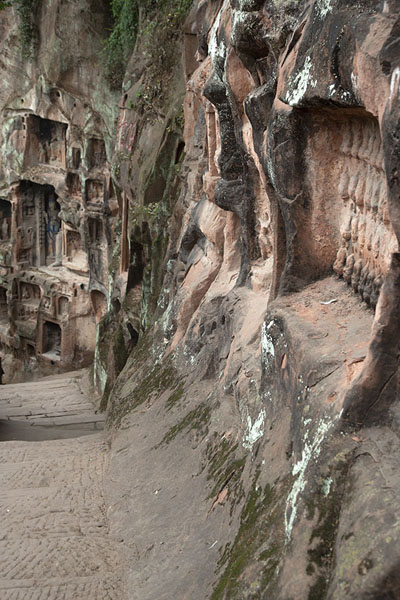 Foto van Looking along the cliff with tens of niches with Buddha statues and scenesJiajiang - China