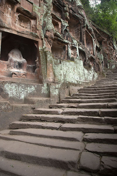 Foto van The stairs leading under the cliff with niches with Buddha figuresJiajiang - China