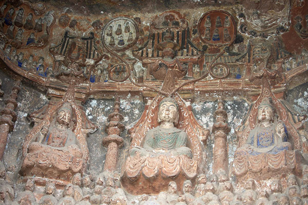 Three Buddha figures surrounded by smaller figures and remnants of paint | Cliff of Thousand Buddhas | China