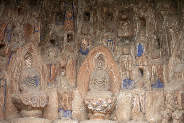 Intricate Buddhist scene with remnants of paint in a niche in the cliff face | Cliff of Thousand Buddhas | China