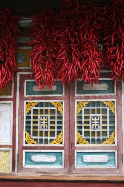 Picture of Jiaju Tibetan village (China): Red peppers hanging under the roof of a richly decorated window