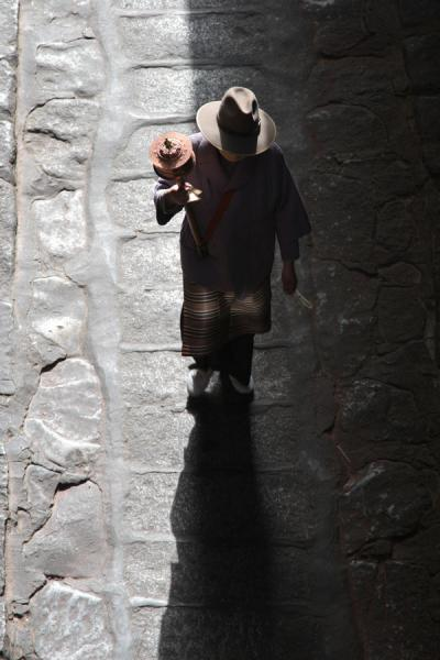 Tibetan pilgrim and shadow on the Nangkhor kora | Jokhang temple | China