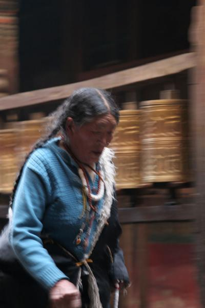 Tibetan woman walking past prayer wheels on Nangkhor kora | Jokhang temple | China