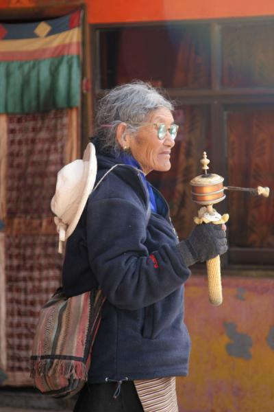 Tibetan woman turning her prayer wheel at Jokhang temple | Jokhang temple | China