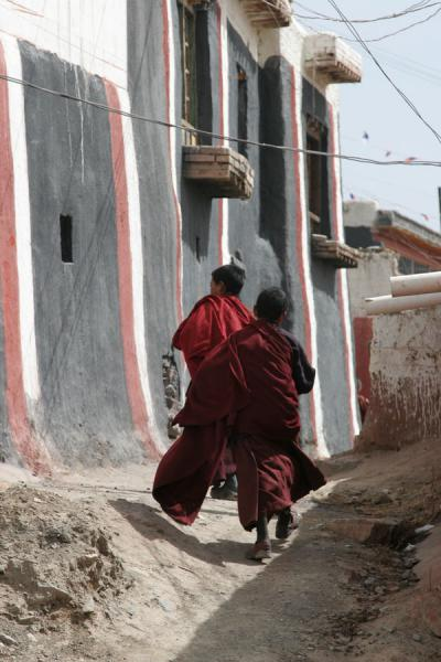 Two young monks running through an alley in Jyekundo Dondrubling | Dondrubling monastery | China