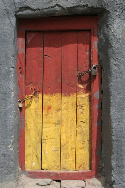 Picture of Dondrubling monastery (China): Painted door in typical dark grey adobe building of Jyekundo monastery