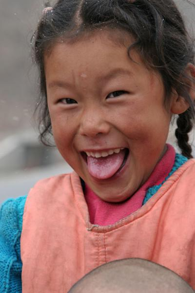 Image of Excited Tibetan girl sticking out her tongue to the photographer,