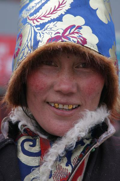 Tibetan woman with typical hood and golden teeth | Jyekundo faces | China