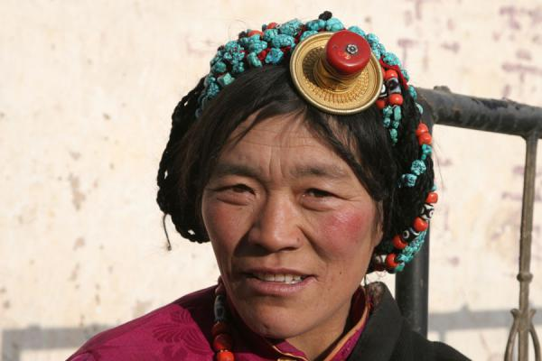 Tibetan woman with typical hair decoration in early morning | Jyekundo faces | China