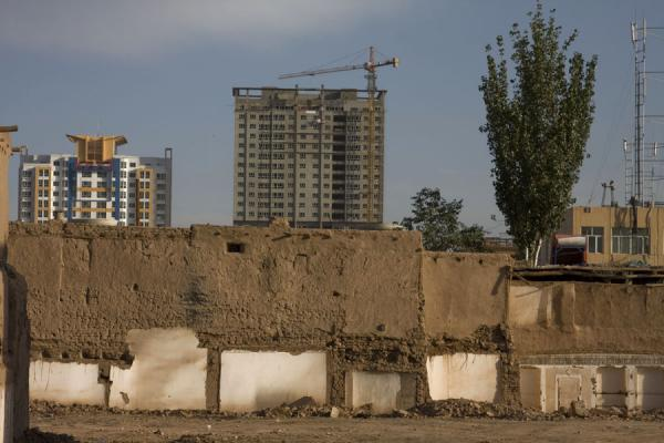 Old and new: remains of house in the old town of Kashgar with modern buildings in the background | Kashgar Old Town | China