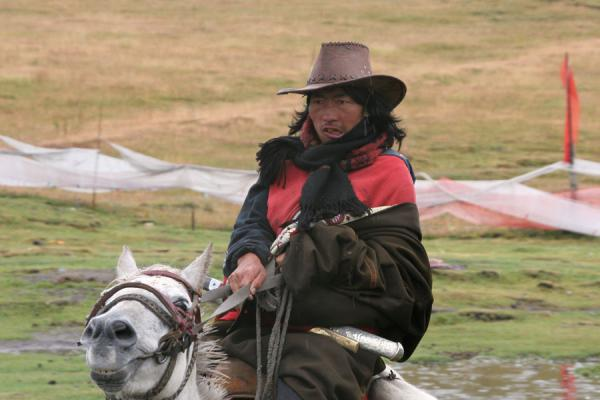 Khampa man horseriding in the vicinity of Tagong | Khampa Tibetans | China