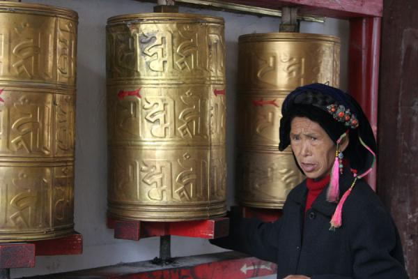 Picture of Khampa Tibetans (China): Khampa woman spinning the prayer wheels of a temple in Kangding