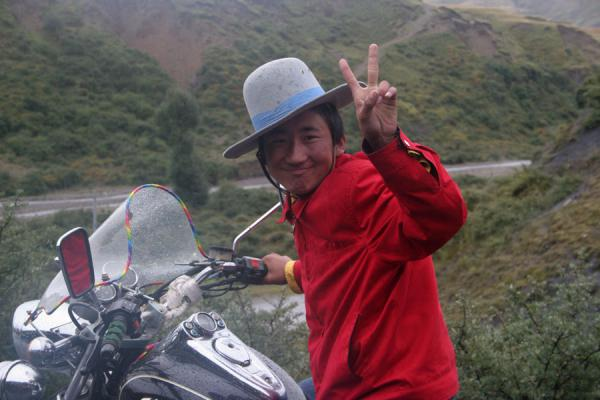 Young Tibetan with common bowler hat on a motorbike | Khampa Tibetans | China