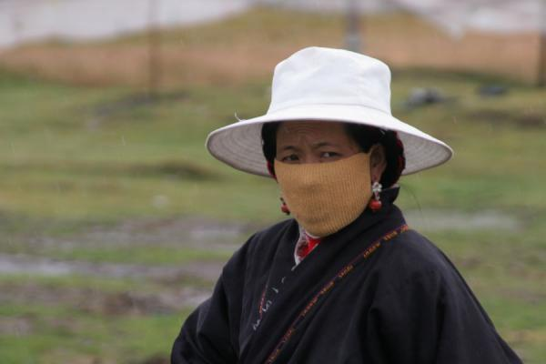 Tibetan woman with white hat and cap in the Kham countryside | Khampa Tibetans | China