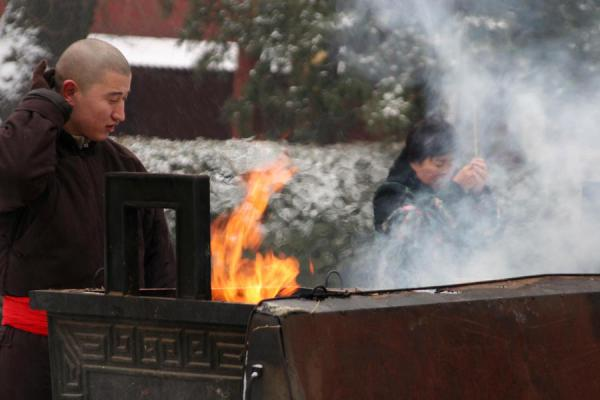 Monk and believer at one of the main incense burners | Lama Temple | China