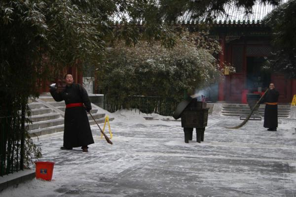 Monk throwing snow in the temple complex | Lama Temple | China