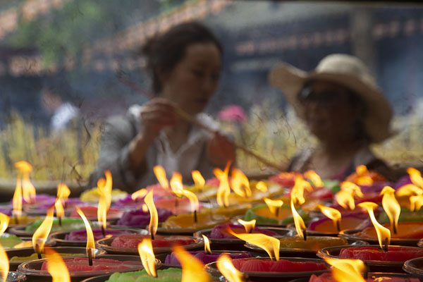 Women lighting a lotus-shaped candle in front of Lingyun temple | Giant Buddha | China