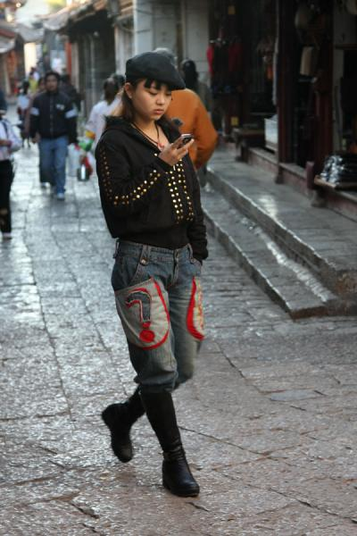 Chinese teenager with her mobile phone in the old town of Lijiang | Lijiang Old Town | China