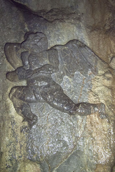 Close-up of a winged figure sculpted out of a wall inside a cave at the Lingyin temple complex | Lingyin temple complex | China