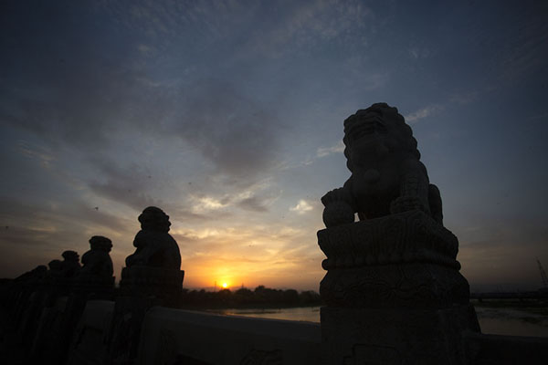 Foto van Sunset over Marco Polo Bridge with the silhouettes of lionsWanping - China