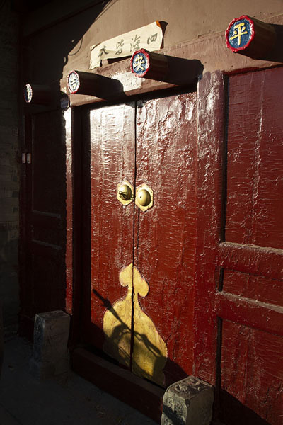 Afternoon sun shining on a dark red door | Nanluogu hutongs | Cina