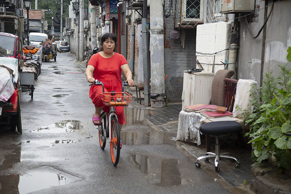 Picture of Woman in red riding her bike through a hutong