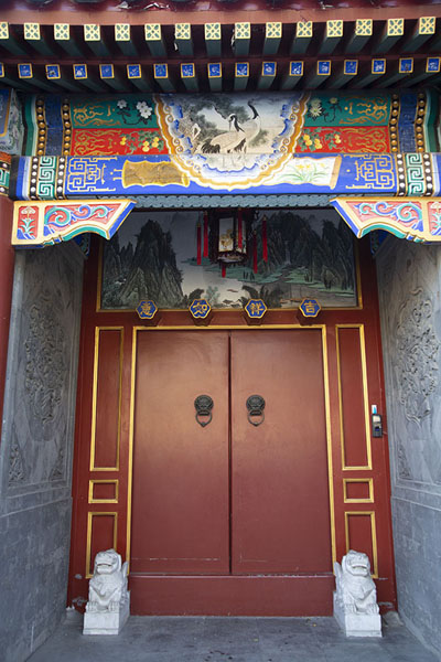 Portal with red doors and finely decorated panel above the entrance | Nanluogu hutongs | China