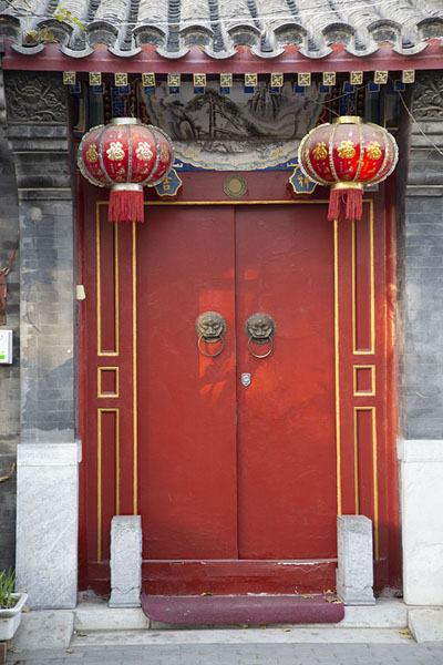 Foto van Lampoons adorning these red wooden doors - China - Azië