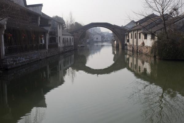 Foto van One of the arched bridges reflected in a canal in Nanxun - China