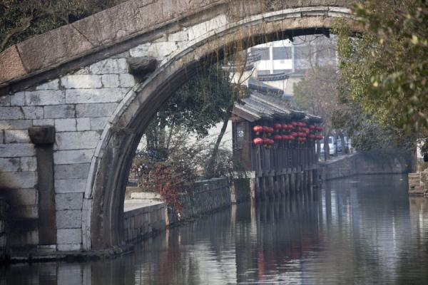 Foto van Looking under a bridge over a canal in the old town of Nanxun - China