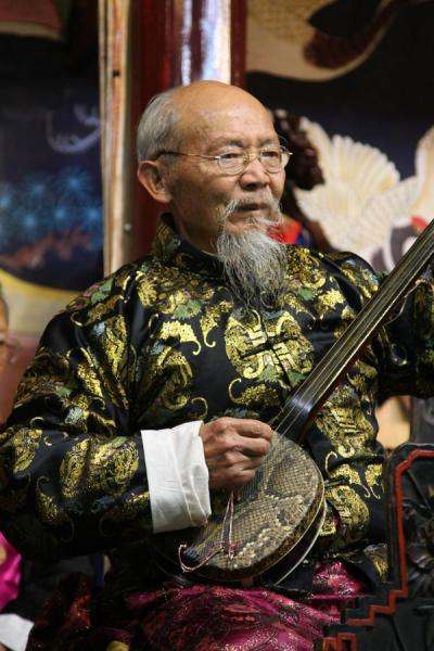 Playing a traditional instrument in the Naxi Orchestra |  | 中国