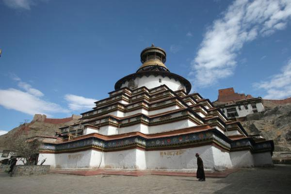 Picture of Pelkor Chöde monastery (China): Tibetan pilgrim walking past the famous Gyantse Kumbum