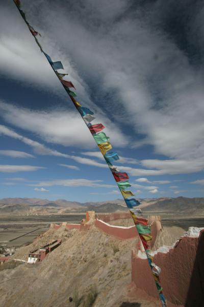 Picture of Pelkor Chöde monastery (China): Prayer flags flying over the Thangka wall of Pelkor Chöde monastery