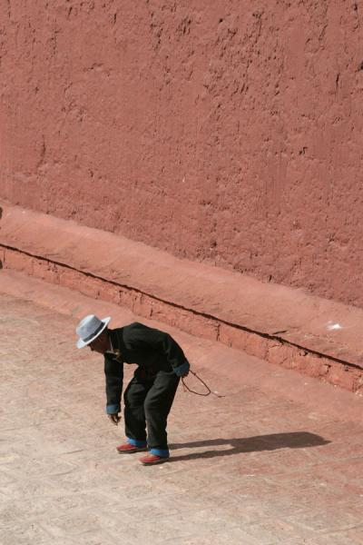 Picture of Pelkor Chöde monastery (China): Pilgrim bending down on kora around main temple of Pelkor Chöde monastery