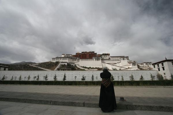 Picture of Praying Tibetan pilgrim praying in front of Potala palace