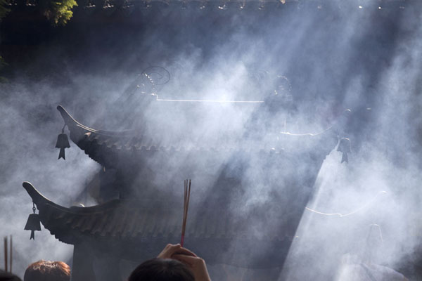 Sunlight filtering through smoke of burning incense | Putuoshan | China