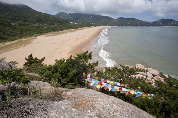 Foto van Thousand Step Beach with prayer flags in the foregroundPutuoshan - China
