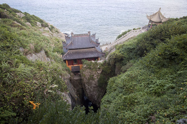 Foto van Temple at Fanyin Cave, straddling a narrow chasm in which the waves produce chant-like soundsPutuoshan - China