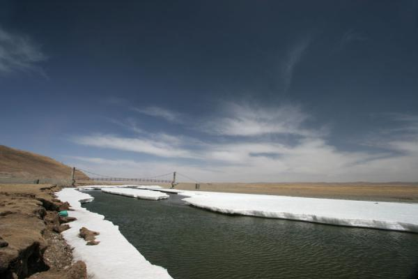 Picture of Qinghai landscape (China): Bridge over river with ice under a blue sky with clouds