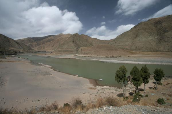 Picture of Qinghai landscape (China): Trees and Yangste river with barren mountains in Qinghai landscape