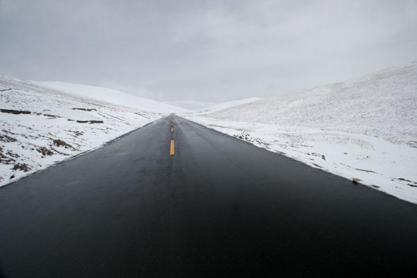 Black asphalt running through a white landscape on the Tibetan highlands of Qinghai province | Qinghai paesaggio | Cina